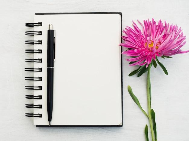 Pusty notatnik, długopis i piękny kwiat