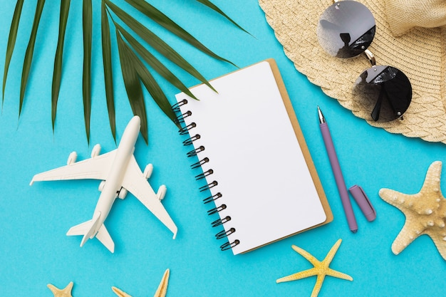 Pusty notatnik długopis zabawka samolot i okulary przeciwsłoneczne na niebieskim tle
