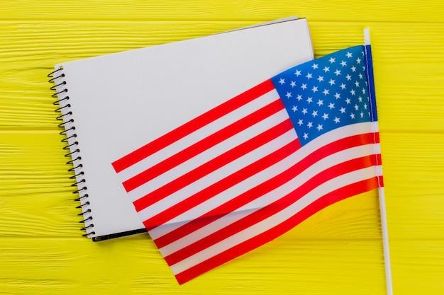 Pusty notatnik do przestrzeni kopii i mieszkania z usa. żółty drewniany stół.