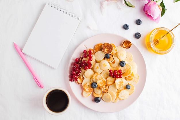 Pusty notatnik do tekstu. malutkie naleśniki z jagodami. koncepcja śniadania, trendy żywieniowe, styl życia. skopiuj miejsce