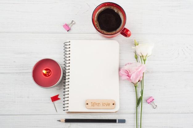 Pusty notatnik, filiżanka kawy, zapalona świeca, kwiaty