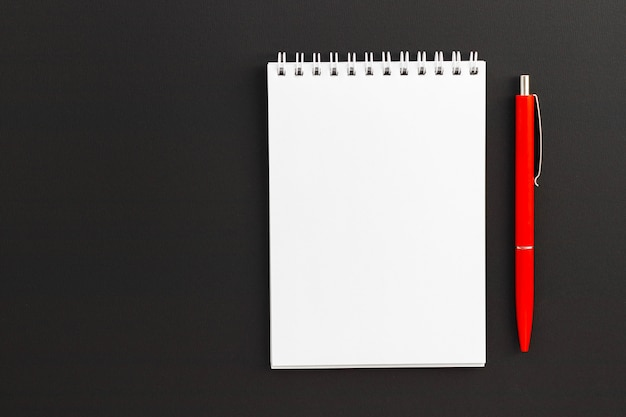 Pusty notatnik i czerwony długopis na czarnym tle. notatnik na notatki i pomysły. widok z góry, płaski układ z miejscem na kopię.