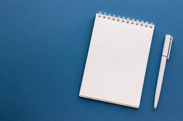 Pusty notatnik i długopis na modnym ciemnym niebieskim tle. notatnik dla wiadomości, lista pomysłów i inspiracji. widok z góry, leżał płasko z miejsca kopiowania. makieta do swojego projektu.