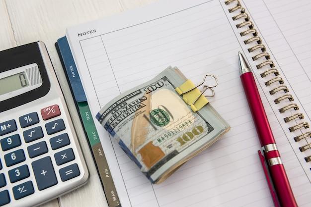 Pusty notatnik i dolar z piórem do projektowania. pomysł na biznes