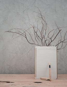 Pusty notatnik i drewniane pióro na drewnianym stole z drewna tekowego