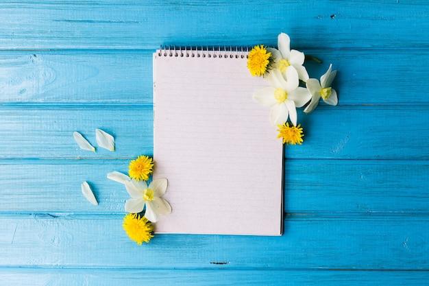 Pusty notatnik i dzikie kwiaty na niebieskim tle drewnianych. koncepcja kwiaty wiosny,