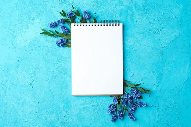 Pusty notatnik i świezi hiacynty na błękitnym stole