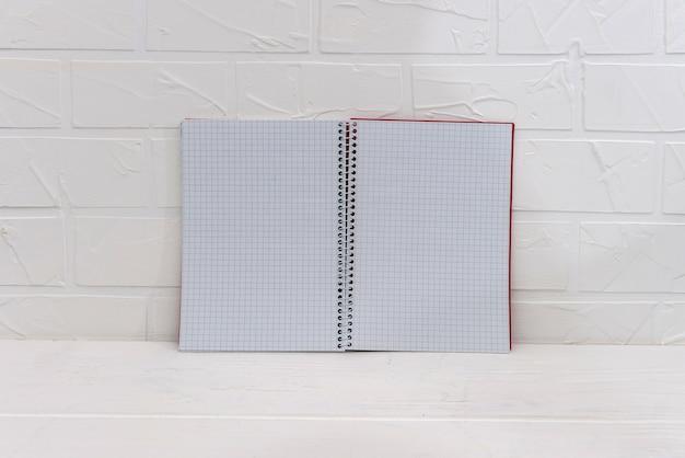 Pusty notatnik na białym tle ściany z cegły