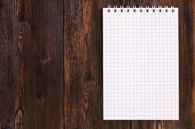 Pusty notatnik na ciemnym drewnianym tle, kopia przestrzeń
