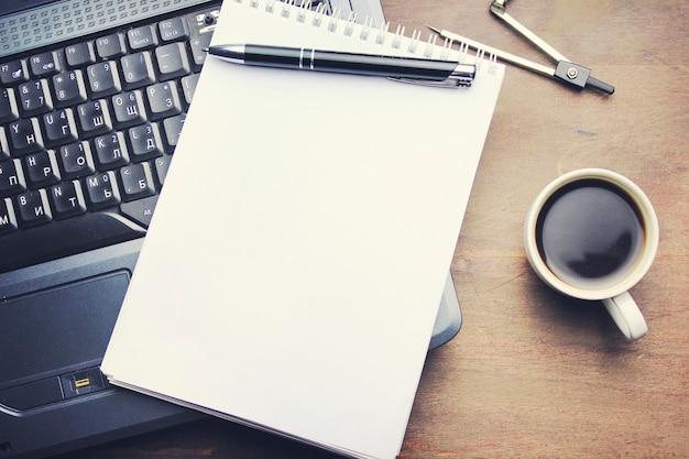 Pusty notatnik na laptopie i kawa na drewnianym stole