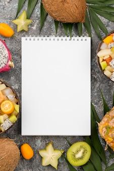 Pusty notatnik otoczony egzotycznymi owocami
