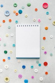Pusty notatnik otoczony kolorowymi guzikami