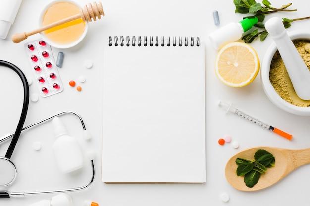 Pusty notatnik otoczony naturalnymi i medycznymi zabiegami