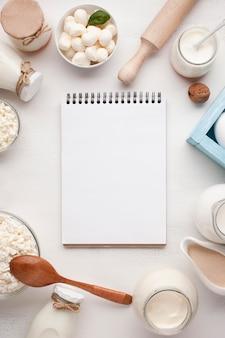 Pusty notatnik otoczony produktami mlecznymi