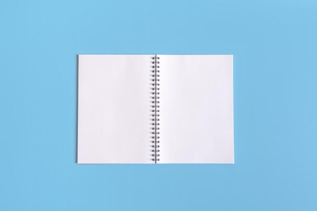 Pusty notatnik otwarty na niebieskim tle