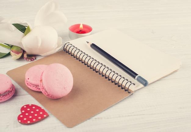 Pusty notatnik, różowe makaroniki, zapalona świeca
