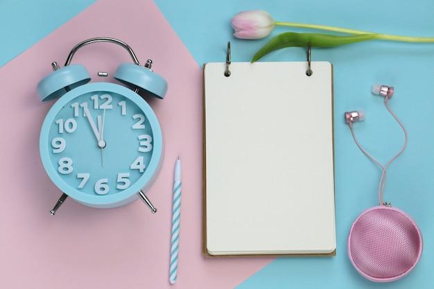Pusty notatnik, słuchawki i kwiat tulipana na różowym niebieskim pastelowym tle