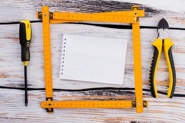 Pusty notatnik w kwadracie linijki z narzędziami naprawczymi. widok z góry na płasko. białe drewniane tło.