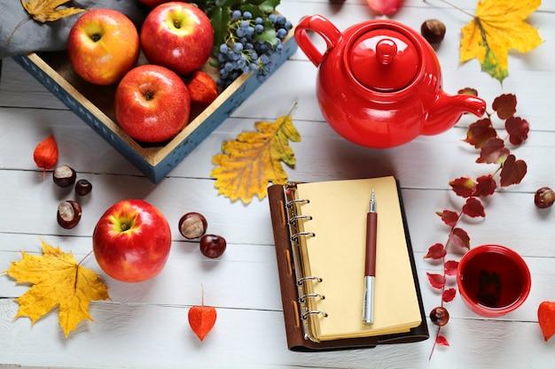 Pusty notatnik z czerwonym czajnikiem i filiżanką z herbatą