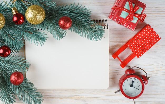 Pusty notatnik z dekoracją świąteczną. choinka gałęzie z czerwoną i złotą kulką