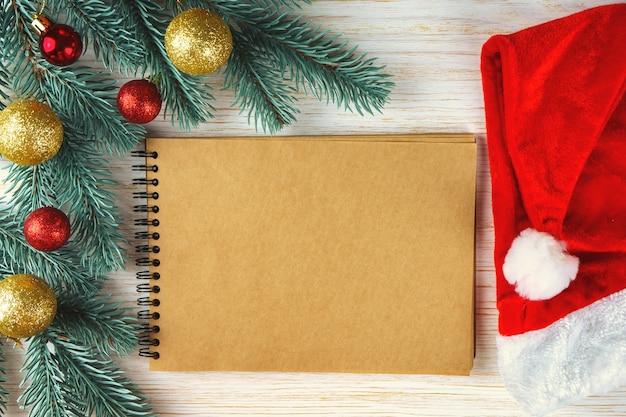 Pusty notatnik z dekoracją świąteczną. choinka gałęzie z czerwonymi i złotymi kulkami
