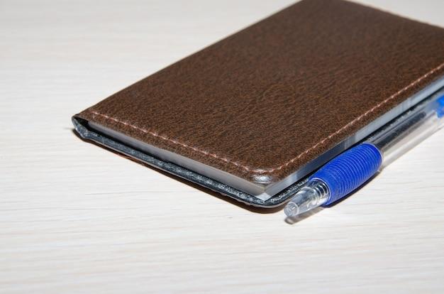 Pusty notatnik z długopisem i ołówkiem na biurowym drewnianym stole