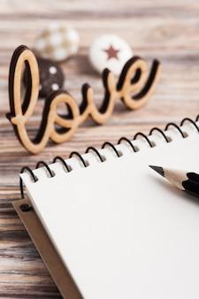 Pusty notatnik z drewnianym znakiem miłość