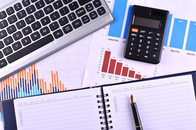 Pusty notatnik z kalkulatorem, klawiaturą i wiecznym piórem na wykresach, wykresach i stole biznesowym. miejsce pracy ludzi biznesu