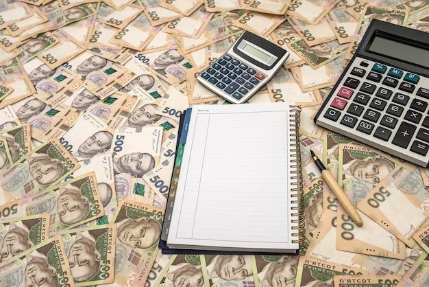 Pusty notatnik z kalkulatorem na tle ukraińskich pieniędzy. 500 banknotów. hrywna (uah). widok z góry.