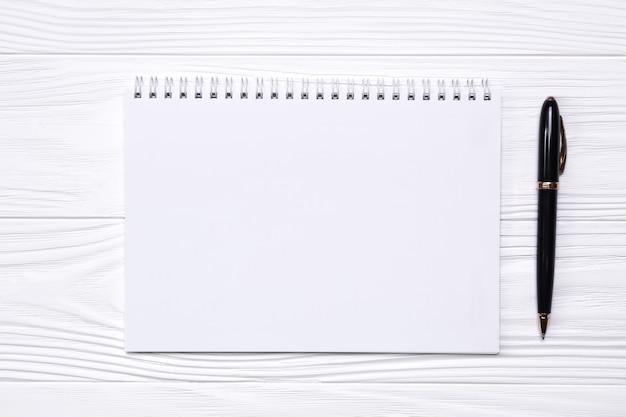 Pusty notatnik z miejscem na tekst i długopis na białym tle drewnianych.