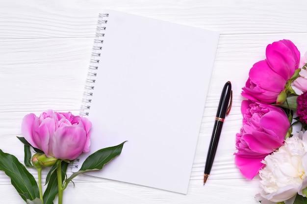 Pusty notatnik z miejscem na tekst i kwiaty piwonie na białym tle drewnianych. widok z góry.
