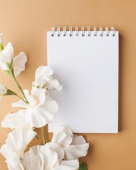 Pusty notatnik z miejscem na tekst w białe kwiaty na jasnobrązowej powierzchni