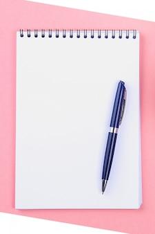 Pusty notatnik z niebieskim piórem na różowym pastelowym tle. makieta, rama, szablon.