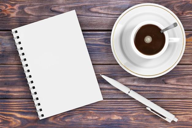 Pusty notatnik z piórem i filiżanką kawy na drewnianym stole. renderowanie 3d
