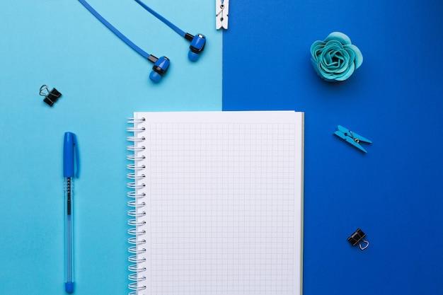 Pusty notatnik z piórem i słuchawkami na niebieskim tle. wolne miejsce na tekst, reklamę.