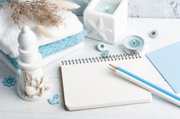 Pusty notatnik z ręcznikami i zapalona świeca jako dekoracja