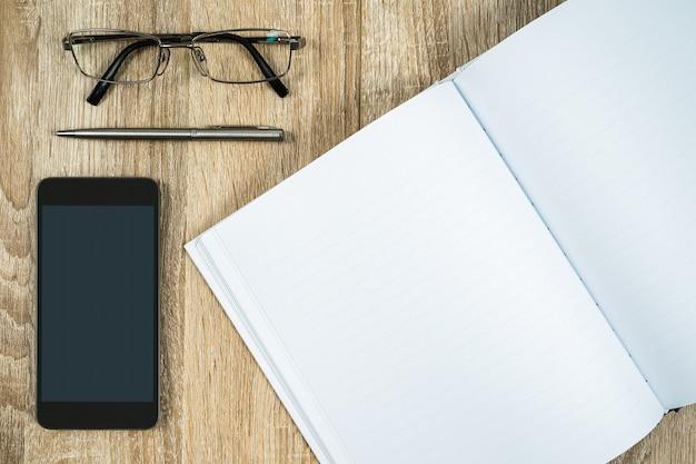 Pusty notatnik z telefonu komórkowego i okularów
