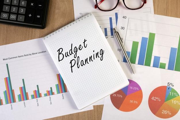 Pusty notatnik z wykresami finansowymi, okularami, długopisem i kalkulatorem w miejscu pracy. widok z góry.