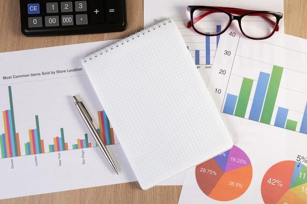 Pusty notatnik z wykresami finansowymi, okularami, długopisem i kalkulatorem w miejscu pracy