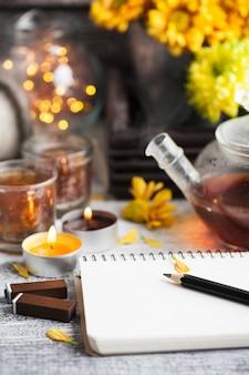 Pusty notatnik z zapalonymi światłami i dzbankiem do herbaty
