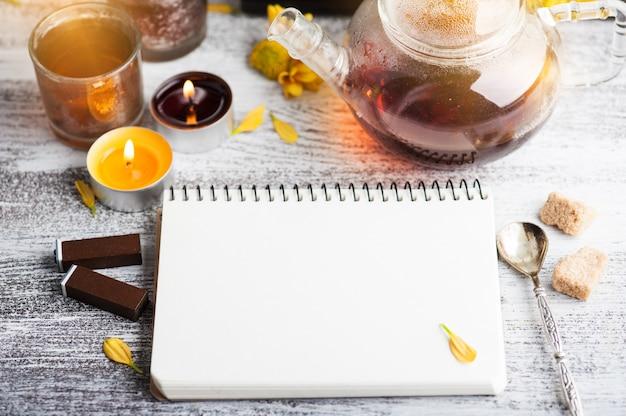 Pusty notatnik z zapalonymi świeczkami i dzbankiem do herbaty