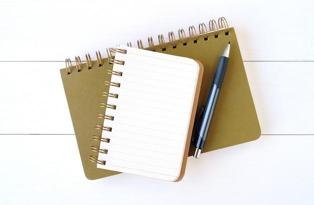 Pusty notatnika papier, pióro na białym drewnianym tle i