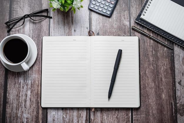 Pusty notebook szklanki kawy długopis widok z góry drewniany stół. skopiuj miejsce.
