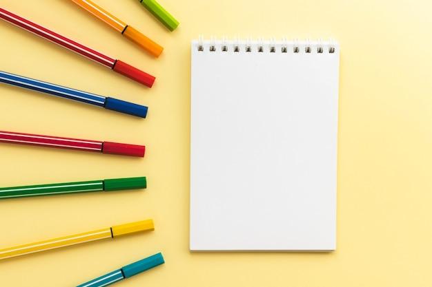 Pusty notes i kolorowe pisaki. wielokolorowe markery do rysowania dzieci. leżał płasko, kopia przestrzeń.