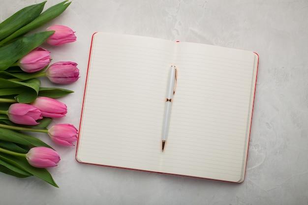 Pusty notes z piórem i tulipanami.