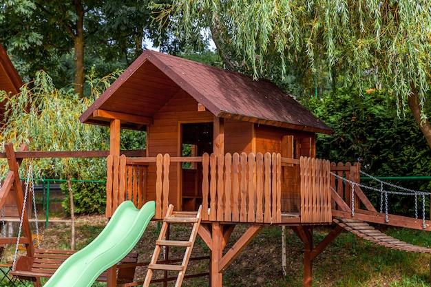 Pusty nowoczesny drewniany plac zabaw dla dzieci na zielonym podwórku w publicznym parku w letni dzień.