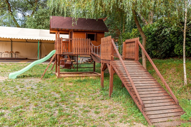 Pusty nowoczesny drewniany plac zabaw dla dzieci na zielonym podwórku w publicznym parku