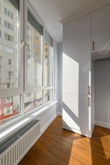 Pusty, ogrzewany penthouse lub salon w domku z drewnianą podłogą i oknami o pełnej wysokości oraz wbudowaną szafą
