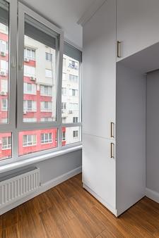 Pusty, ogrzewany salon na najwyższym piętrze z oknami od podłogi do sufitu