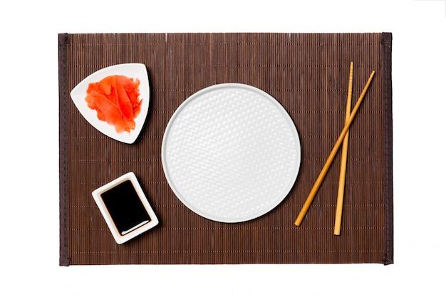 Pusty okrągły biały talerz z pałeczkami do sushi, imbiru i sosu sojowego na ciemnej bambusowej macie.
